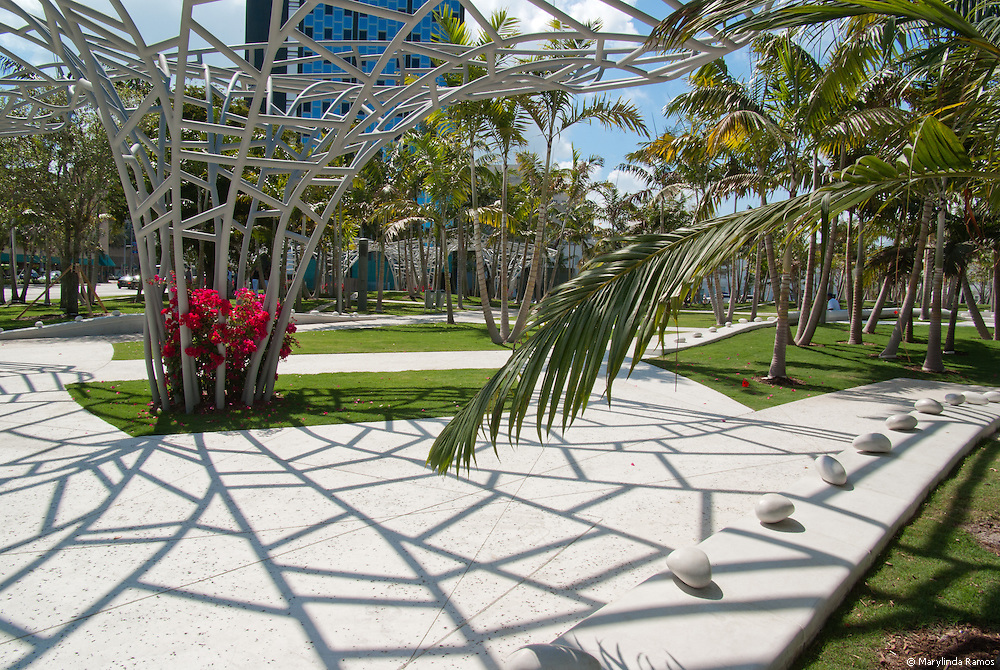 Metal flower sculptures contribute their web of shade to that of graceful palms.  White paths with white stone benches separated by large white polished pebbles invite reflection in a green landscape punctuated with fuschia bougainvillea.  Don your ipod and download your latest favorite from New World Symphony's eclectic repertoire.