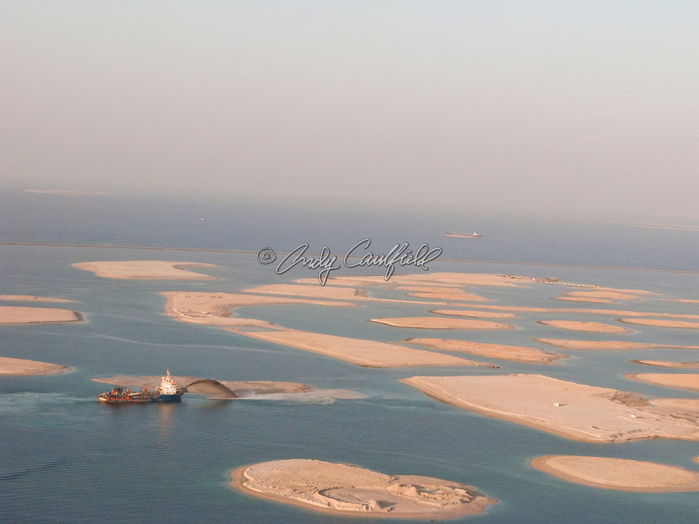 "Aerial view of a dredge forming an island with reclaimed sand using a technique known as ""rainbowing"". This group of islands is part of ""The World"" a man-made archipelago of 300 islands in the shape of a world map. Located off the cosat of Dubai in the Persian Gulf it will eventually feature entrainment, commercial and residentail properties. Dubai, United Arab Emirates (UAE)"
