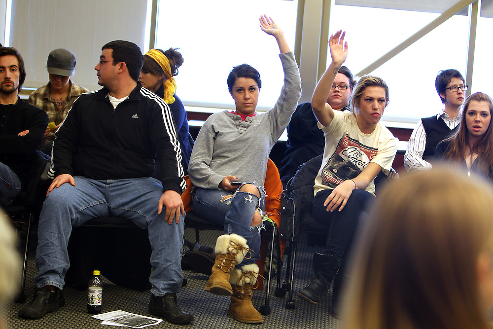 3/7/11 5:14:48 PM -- Minneapolis, MN, U.S.A.---.Maddie Johnson, 21, center, of St. Cloud, MN, and Lauren Anderson, 21, third from right, of West Bloomfield, MI, raise their hands to volunteer during a StepUP all-house weekly Circle meeting at Augsburg College in downtown Minneapolis March 7, 2011..---.Photo by Courtney Perry, Freelance.