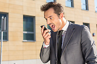 Angry businessman screaming at mobile phone against office building