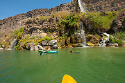 Woman with dog kayaking under a waterfall on the Snake River canyon near Twin Falls, Idaho. MR