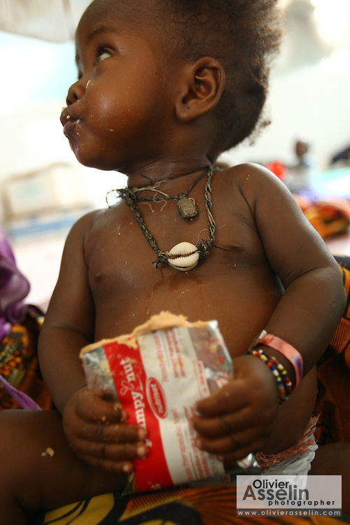 One-month-old Isatu Kamara enjoys a packet of Plumpy Nut therapeutic food at the therapeutic feeding center of the Megbenthe hospital in Makeni, Sierra Leone, on Friday February 27, 2009. UNICEF sponsored some of the construction of the facilities, and also provides high-protein biscuits and milk as part of a joint effort with the World Food Programme.