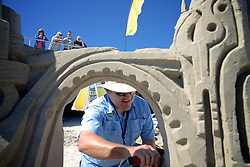 From the boardwalk a group watches how Rusty Croft is sculpting a sandcastle. Croft, who is a professional sand-sculptor from Carmel, CA tells that the quality of the sand at the beach allows him to do all sorts of crazy stuff. (Bas Slabbers/for NewsWorks)