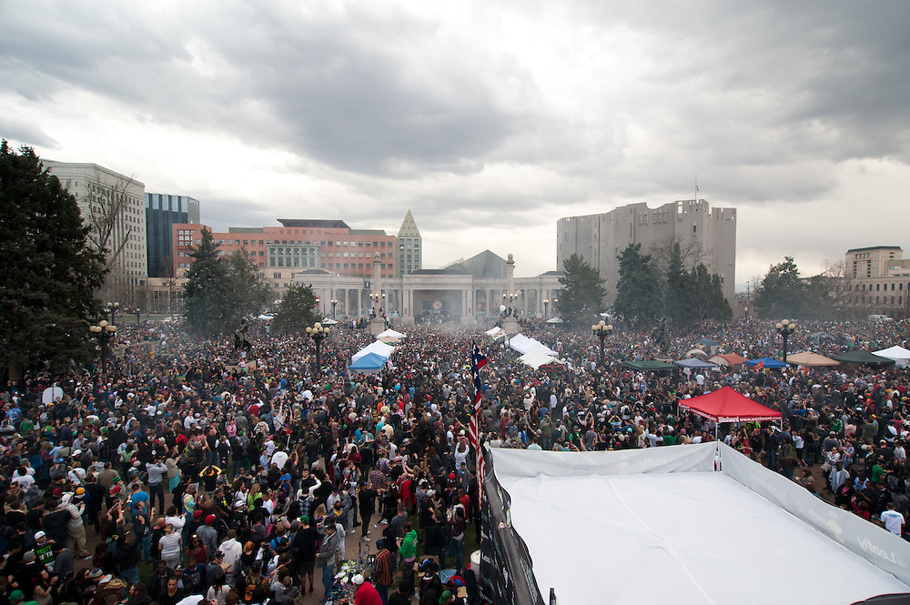 Smoke rises at 4:20 as thousands of participants smoke marijuana at the Civic Center Park rally. The ampitheatre, center, was later the site of a shooting.