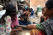 Azharuddin Ismail, 10, the child actor playing the role of 'young Salim', the brother of Jamal, protagonist of Slumdog Millionaire, the famous movie winner of 8 Oscar Academy Awards in December 2008, is listening to music through his mobile phone in the slum where he still lives with his family next to the train station of Bandra (East), Mumbai, India. Various promises were made to lift the two young actors (Azharuddin Ismail and Rubina Ali) from poverty and slum-life but as of the end of May 2009 anything is yet to happen. Rubina's house was recently demolished with no notice as it lay on land owned by the Maharashtra train authorities and she is now permanently living with her uncle's family in a home a stone-throw away in the same slum. Azharuddin's home too was demolished in the past two weeks, as it happens every year in his case, because the concrete walls were preventing local authorities to clear a drain passing right behind it. As usual, his father is looking into restoring the walls as soon as the work on the drain has been completed.