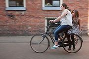 Een meisje fietst met een ander meisje achterop door Groningen. <br /> <br /> Two girls are riding on a bicycle in Groningen.