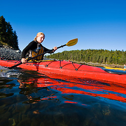 A woman sea kayaking near the Porcupine Islands in Maine's Acadia National Park.  Frenchman Bay.  Bar Harbor. Rum Key.