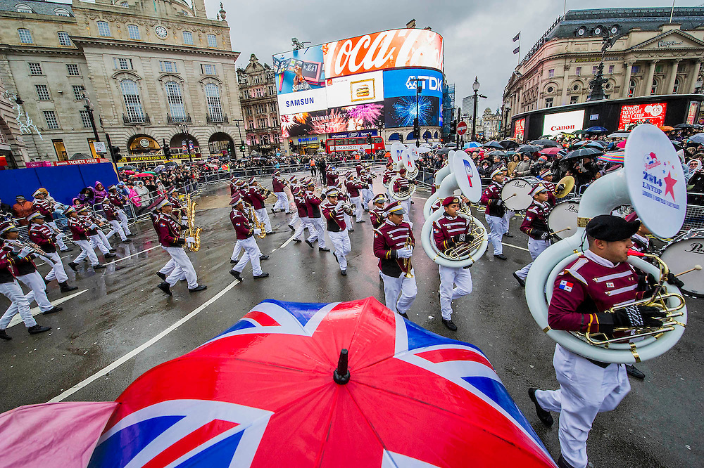A new year's day parade passes through Piccadilly Circus on a wet and windy day. London, UK 01 Jan 2014.