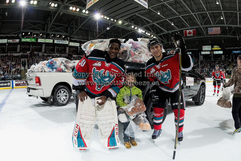 KELOWNA, CANADA - DECEMBER 3: Michael Herringer #30 and Jordan Borstmayer #11 of the Kelowna Rockets pose on the ice with a young fan during the annual teddy bear toss against the Brandon Wheat Kings on December 3, 2016 at Prospera Place in Kelowna, British Columbia, Canada.  (Photo by Marissa Baecker/Shoot the Breeze)  *** Local Caption ***