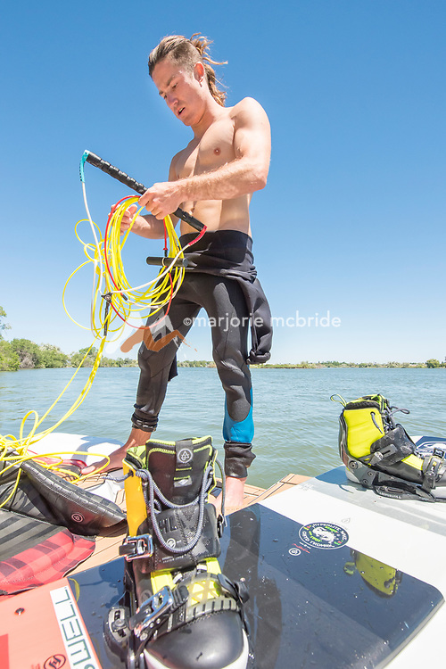 Male athlete on jet boat preparing to wake board on the Snake River in Burley, Idaho.