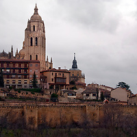 The city of Segovia, Spain surrounded by its ancient protective wall and the Cathedral of Segovia rising above.