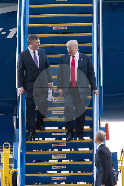 U.S. President Donald Trump walks down the steps with Boeing Commercial Aircraft CEO Kevin McAllister, left, as Boeing CEO Dennis Muilenburg, right, waits at the bottom after touring the new Boeing 787-10 Dreamliner aircraft at the Boeing factory February 17, 2016 in North Charleston, SC. Trump is at the factory for the rollout of the new aircraft.