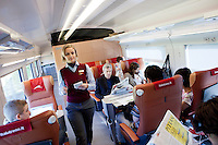 Florence, Italy - 28 April, 2012: A hostess walks by first class passengers on the Milano bound ITALO, Europe's first private operator of high-speed, domestic trains in Italy, in Florence, Italy, on April 28, 2012. The company's president is Ferrari chairman Luca Cordero di Montezemolo, one of the shareholders along with other private entrepreneurs like luxury businessmen Diego Della Valle, the French railway company, Italy's largest retail bank and the country's largest insurer. Italy's NTV (Nuovo Trasporto Viaggiatori) is the first company in Europe to compete with the state-run Trenitalia on high-speed service. When at full regime at the end of the year, 25 innovative trains will connect nine Italian cities, from Salerno to Milan, from Turin to Venice at 300km per hour. Italo passengers will board on stable trains that do not rely on a locomotive car, but has engines underneath each of the 11 carriages to increase capacity as well as safety.<br /> <br /> Ph. Gianni Cipriano for The New York Times