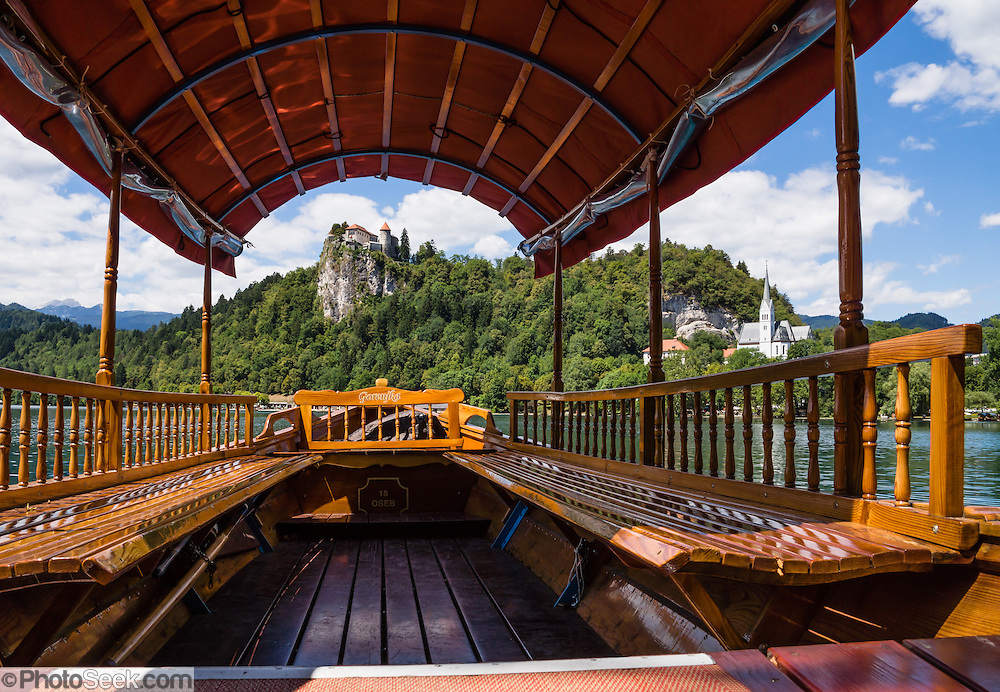 """The distinctive Pletna boats on Lake Bled can carry 20 people in their handsome wooden interior, designed in 1590. A colourful awning protects passengers from sun and weather. Pletna boats carry tourists across Lake Bled under the medieval Bled Castle (Slovene: Blejski grad, German: Burg Veldes), which was built a little before 1011 AD on a cliff above the city of Bled, in what is now Slovenia, Europe. Visitors enjoy riding the two-paddle Pletna boats to Bled Island (Blejski otok, the only natural island in Slovenia), upon which stands the Pilgrimage Church of the Assumption of Mary (Slovenian: Cerkev Marijinega vnebovzetja), built in the 1400s and now popular for romantic weddings. The respected title of """"Pletnarstvo,"""" Pletna oarsman, has been handed down within specific families from generation to generation."""