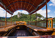 "The distinctive Pletna boats on Lake Bled can carry 20 people in their handsome wooden interior, designed in 1590. A colourful awning protects passengers from sun and weather. Pletna boats carry tourists across Lake Bled under the medieval Bled Castle (Slovene: Blejski grad, German: Burg Veldes), which was built a little before 1011 AD on a cliff above the city of Bled, in what is now Slovenia, Europe. Visitors enjoy riding the two-paddle Pletna boats to Bled Island (Blejski otok, the only natural island in Slovenia), upon which stands the Pilgrimage Church of the Assumption of Mary (Slovenian: Cerkev Marijinega vnebovzetja), built in the 1400s and now popular for romantic weddings. The respected title of ""Pletnarstvo,"" Pletna oarsman, has been handed down within specific families from generation to generation."
