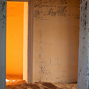 Light from a room beyond, in a sand-filled abandoned home in Kolmanskop, Namibia