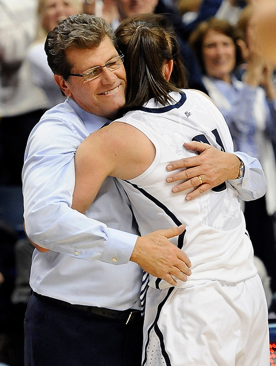 Connecticut coach Geno Auriemma, left, hugs Connecticut's Kelly Faris during the second half of an NCAA college basketball game in Storrs, Conn., Monday, Jan. 21, 2013. Faris had 18 points and 12 rebounds in Connecticut's 79-49 win over Duke. (AP Photo/Jessica Hill)