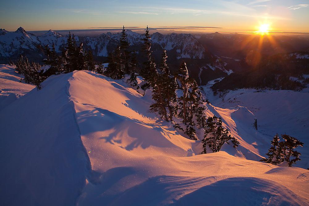 A setting sun illuminates a windswept ridge above Paradise in Mount Rainier National Park, Washington.