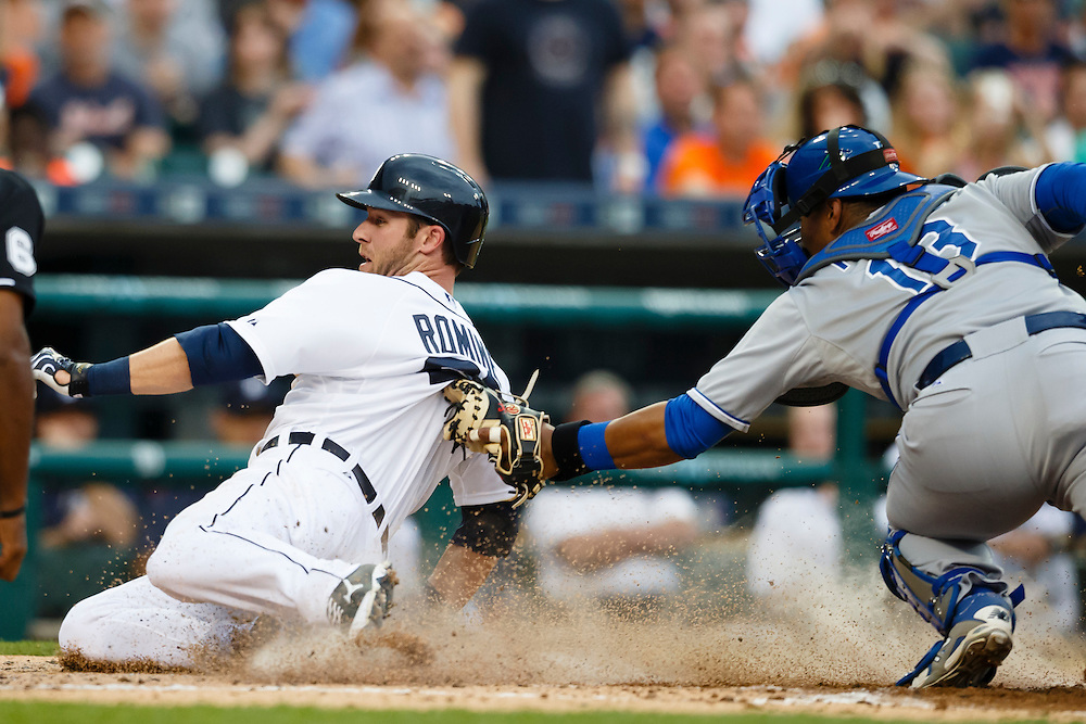 May 8, 2015; Detroit, MI, USA; Detroit Tigers third baseman Andrew Romine (27) slides in safe at home on Kansas City Royals catcher Salvador Perez (13) in the second inning at Comerica Park. Mandatory Credit: Rick Osentoski-USA TODAY Sports