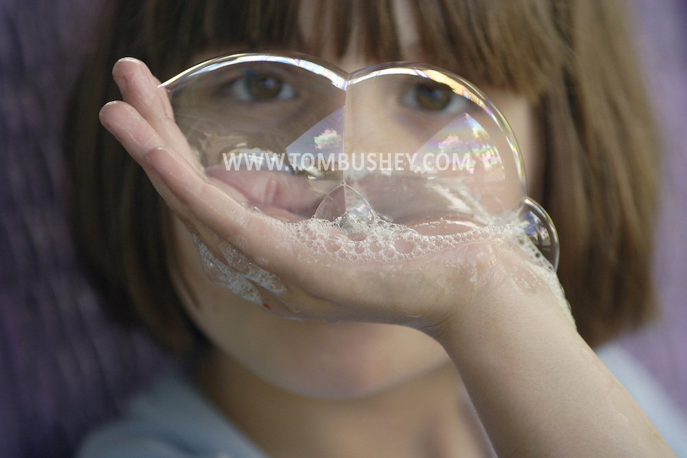 Middletown, NY  - An 8-year-old girl looks through bubbles she blew on June 27, 2007.