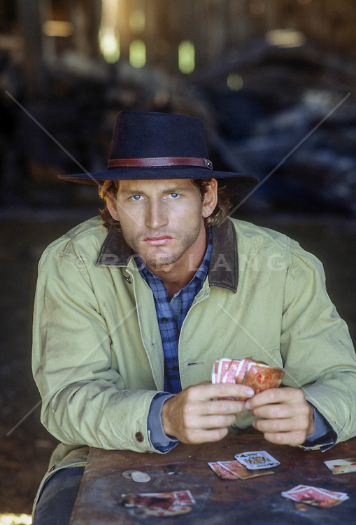 mean looking cowboy playing cards with a dirty deck inside a barn