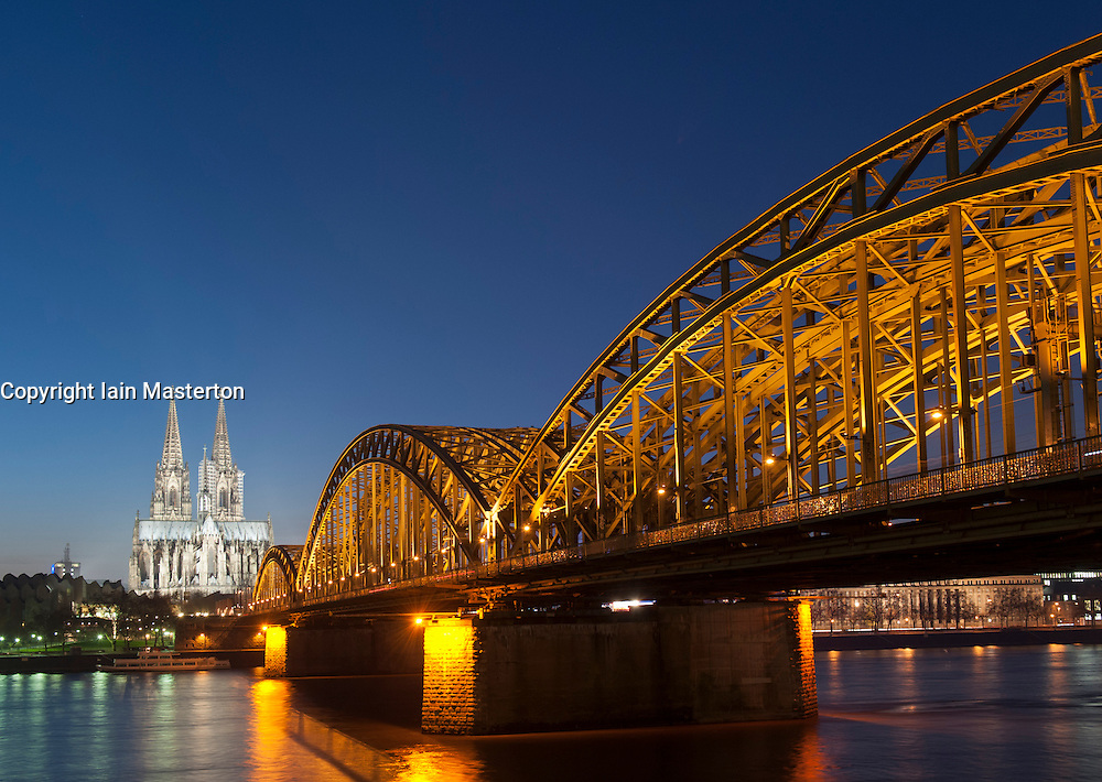 Night view of Cologne Cathedral and Hohenzollern Bridge across the River Rhine in Germany