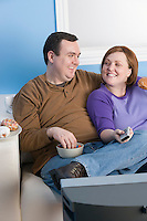 Overweight couple eating on sofa