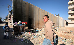 West Bank  - May 6th,  2008 - People walk through the  separation  barrier which runs through Alram  neighbourhood  of  Jerusalem, West Bank, May 6th, 2008. Picture by Andrew Parsons / i-Images