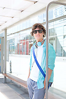 Portrait of confident man waiting at bus stop