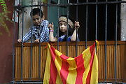 Pakistani children behind a balcony and waving red and yellow striped Catalan flags for Catalan National Day on September 11, 2012, Barcelona, Spain. The severity of the worst economic crisis has fuelled separatism and highlighted fractures between Spain's northeast and the central government in Madrid. National Day, or Diada, in fact, marks the defeat of Catalan forces on September 11, 1714, at the hands of Philip V of Spain after a 13-month siege of Barcelona. Picture by Manuel Cohen