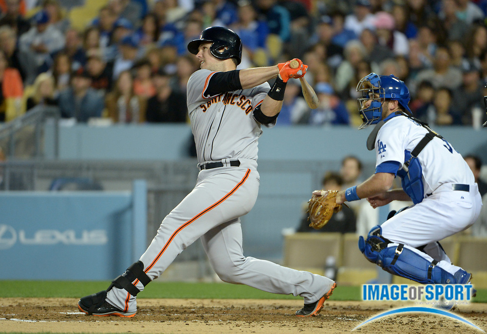 May 8, 2014; Los Angeles, CA, USA; San Francisco Giants catcher Buster Posey (28) bats as Los Angeles Dodgers catcher Drew Butera (31) watches at Dodger Stadium. The Giants defeated the Dodgers 3-1 in 10 innings.