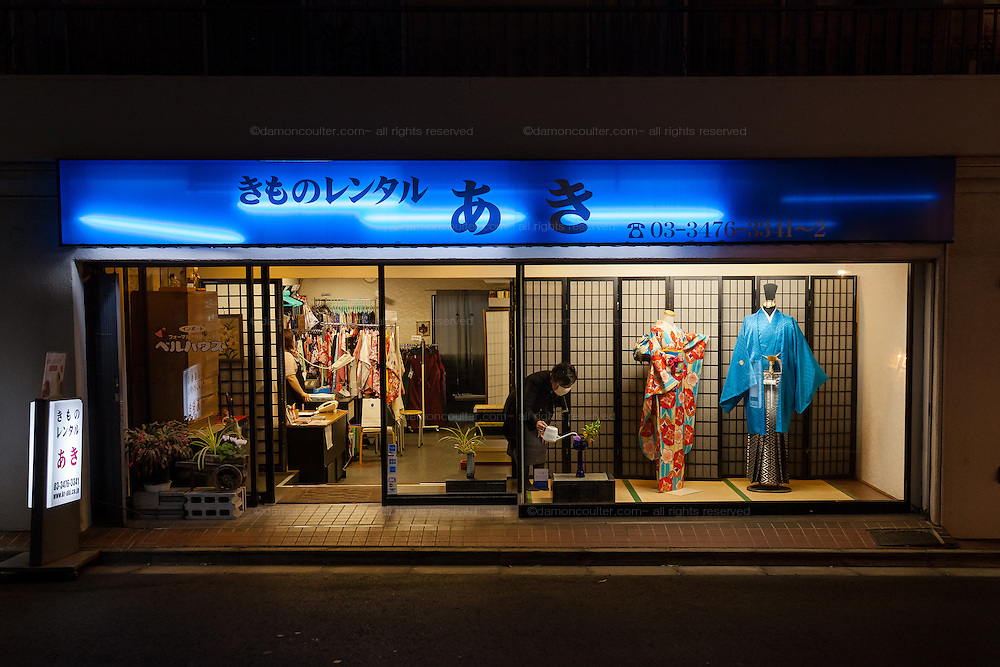 A woman waters a plant in the shop window of a Kimono shop in Dogenzaka, Shibuya, Tokyo, Japan. Friday March 25th 2016