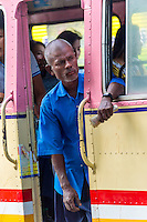 YANGON, MYANMAR - CIRCA DECEMBER 2013: Person peeking outside and looking for passengers on public bus in the city of Yangon in Myanmar
