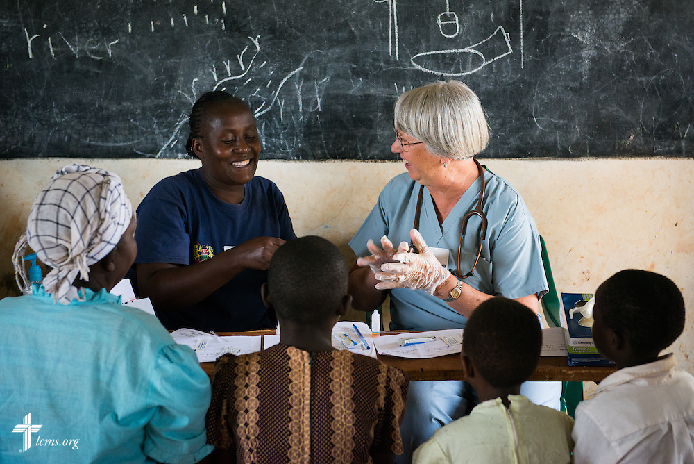 Elga Heintzen, a nurse from Hinsdale, Ill., attending First St. Paul Lutheran Church, works with a Kenyan health worker to learn how to administer Malaria tests during the Mercy Medical Team clinic Wednesday, June 11, 2014, at the Luanda Doho Primary School in Kakmega County, Kenya. LCMS Communications/Erik M. Lunsford