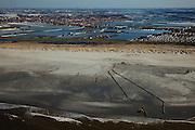 Nederland, Zuid-Holland, 's-Gravenzande, 18-03-2009; Versterking van de kust van Delfland tussen Slag Beukel en Slag Vluchtenburg. In de voorgrond de zandpersleidingen waarmee zand op het strand gespoten is, de zogenaamde zandsuppletie. De kust tussen Hoek van Holland en Den Haag is een van de 'Zwakke Schakels' in de zeewering. Verder is het strand extra verbreed om een nieuwe duinenrij met duinvallei te maken, natuurcompensatie in verband met de aanleg van de Tweede Maasvlakte. Achter de duinen de kassen van het Westland  gezien naar 's-Gravenzande en Naaldwijk..Strengthening of the coast of Delfland between Hoek van Holland and The Hague by means of sand-supplementation. Pipes for transport of sand in the foreground. Extra sand has been applied to make an extra dune valley on the beach. This so-called nature compensation is necessary because of the construction of the nearby Maasvlakte 2 (land reclamation for Port of Rotterdam). Behind the dunes the greenhouses of the Westland area..Swart collectie, luchtfoto (toeslag); Swart Collection, aerial photo (additional fee required); .foto Siebe Swart / photo Siebe Swart