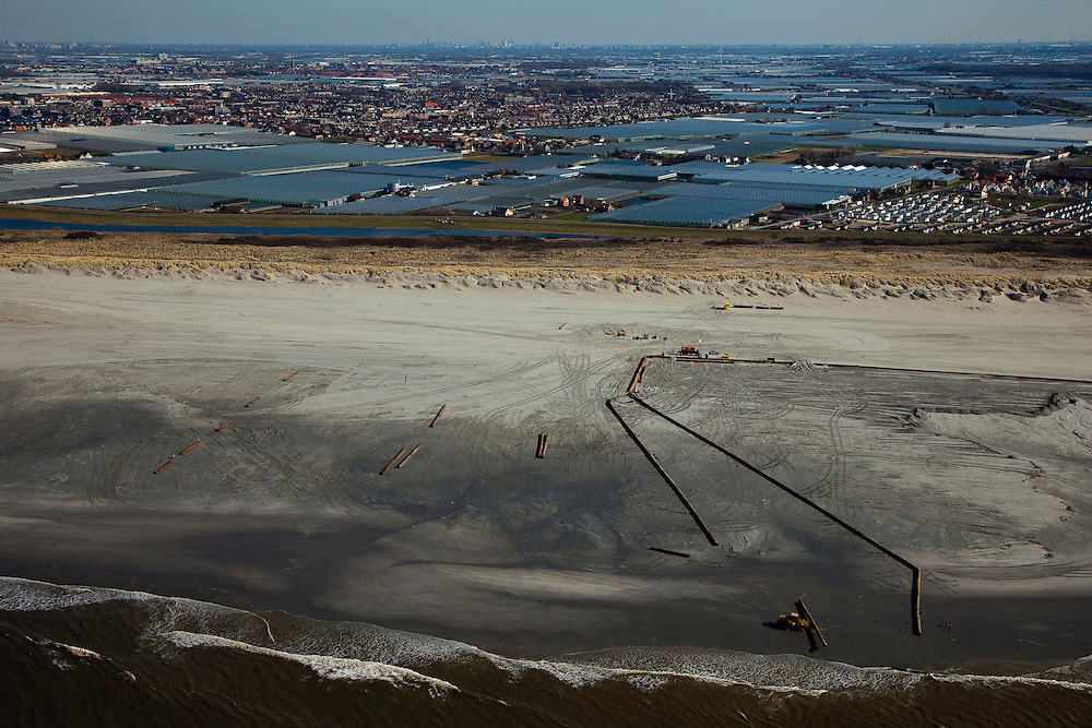 Nederland, Zuid-Holland, 's-Gravenzande, 18-03-2009; Versterking van de kust van Delfland tussen Slag Beukel en Slag Vluchtenburg. In de voorgrond de zandpersleidingen waarmee zand op het strand gespoten is, de zogenaamde zandsuppletie. De kust tussen Hoek van Holland en Den Haag is een van de 'Zwakke Schakels' in de zeewering. Verder is het strand extra verbreed om een nieuwe duinenrij met duinvallei te maken, natuurcompensatie in verband met de aanleg van de Tweede Maasvlakte. Achter de duinen de kassen van het Westland  gezien naar 's-Gravenzande en Naaldwijk..Strengthening of the coast of Delfland between Hoek van Holland and The Hague by means of sand-supplementation. Pipes for transport of sand in the foreground. Extra sand has been applied to make an extra dune valley on the beach. This so-called nature compensation is necessary because of the construction of the nearby Maasvlakte 2 (land reclamation for Port of Rotterdam). Behind the dunes the greenhouses of the Westland area..Swart collectie, luchtfoto (toeslag); Swart Collection, aerial photo (additional fee required); .foto Siebe Swart / photo Siebe Swart