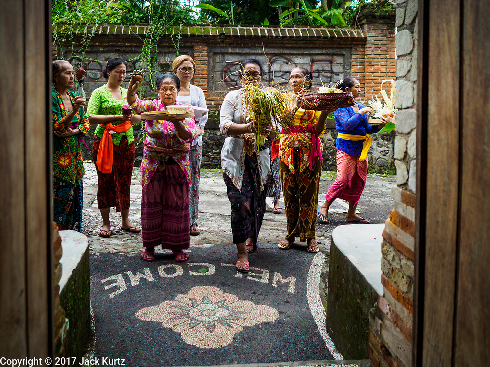 "08 AUGUST 2017 - UBUD, BALI, INDONESIA: Women pray at the entrance of their family compound during a ceremony to honor a family temple in Ubud, Bali. Balinese Hindus have a 210 day calender and every almost every family compound on Bali has a family temple. Once a year (or every 210 days) families celebrate the ""birthday"" of their temple with a ceremony.     PHOTO BY JACK KURTZ"