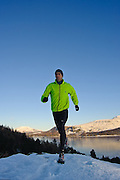A runner in the snow, above Derwent water, and Skiddaw, Lake District, Cumbria, Uk
