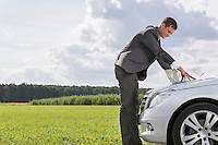 Side view of young businessman looking at map on car hood at countryside