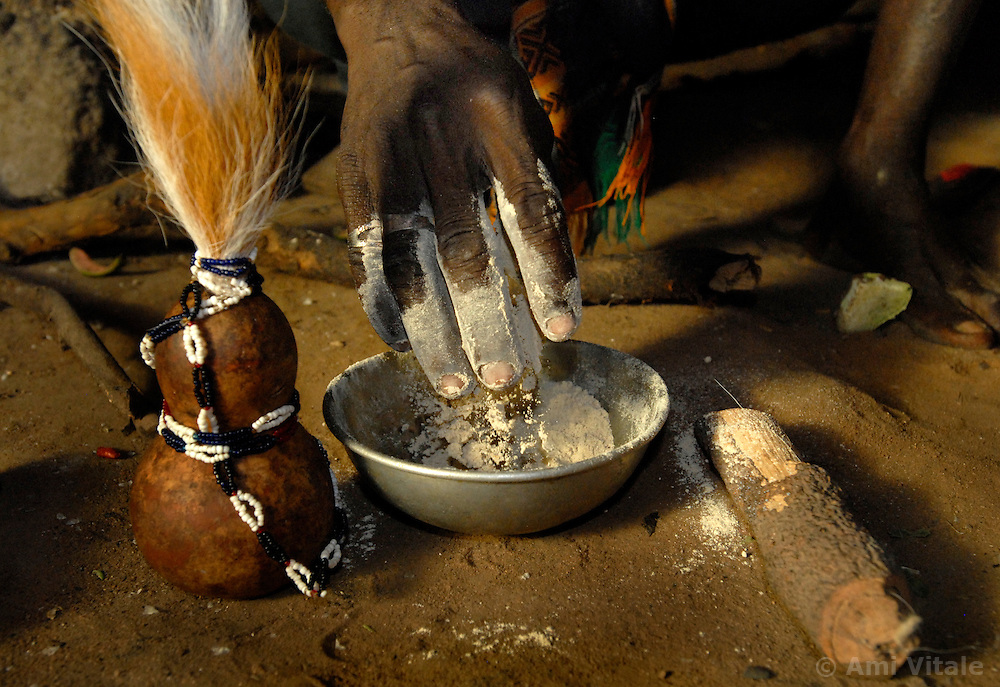"Ahmad Msham, 39, a bush doctor from Chidodo settlement in Lindi, Tanzania prepares a mix using maize flour and tree roots next to a kibuyu vessel that holds lion's hair that he uses for ""white magic"" when spirit lions are thought to be eating villagers. (Photo by Ami Vitale)"