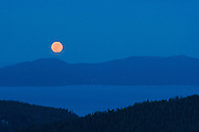 Full moon rising over lake Tahoe as seen from Squaw Valley high camp.
