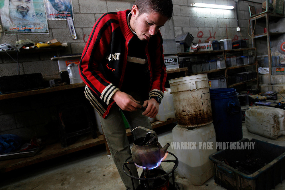 JABALIYA, GAZA STRIP - MARCH 29: Palestinian worker, Ahmed al-Helou (21) melts metal in a tea pot that will be used to make batter contacts at a car-battery workshop, Monday, 29 March, 2010, in Jabaliya, Gaza Strip. Workers at the sales/repair shop have been recycling metal to repair car batteries for more than 10 years, but have seen the number of repairs more than double since the Israeli blockade of Gaza, while their number of new-battery sales have plummeted. The blockade of Gaza has lead to new and innovative ways to recycle materials in order to supply demands, but often at the exploitation of the unemployed who make US$7-14 per day collecting or processing the materials. (Photo by Warrick Page)