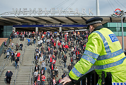 LONDON, ENGLAND - Saturday, April 14, 2012: A policeman watches Liverpool and Everton supporters arrive at Wembley Park Underground Station to watch the 218th Merseyside Derby, the FA Cup Semi-Final, at Wembley. (Pic by David Rawcliffe/Propaganda)