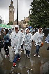 © Licensed to London News Pictures. 02/08/2016. London, UK. Visitors wear plastic ponchos as they walk near Parliament as intermittent rain showers hit the capital. Photo credit: Peter Macdiarmid/LNP