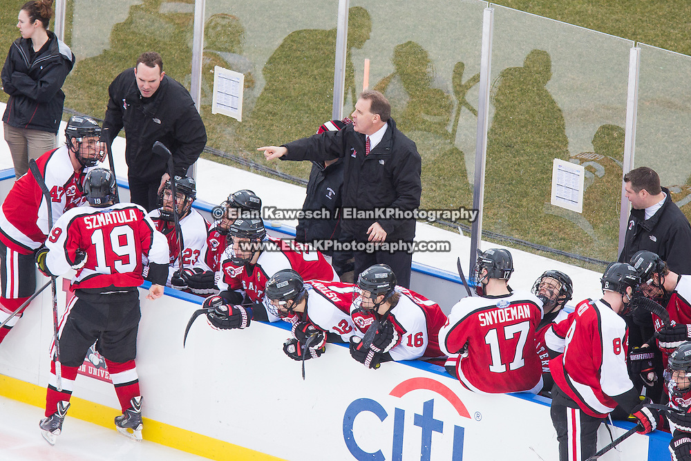 Northeastern coach Jim Madigan speaks with his players during the Frozen Fenway game between The Northeastern Huskies and The UMass Lowell Riverhawks at Fenway Park on January 11, 2014 in Boston, Massachusetts.