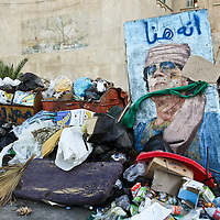 A picture of former Libyan leader Muammar Gaddafi sits beside a pile of trash in Tripoli, Libya. August 2011.