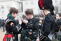© Licensed to London News Pictures. 20/01/2018. London, UK. Student members of the Pipes and Drums Band from Gordon's School in Surrey prepare to lead the annual parade to the national monument to General Gordon of Khartoum. The school is the only one in the country permitted to march along Whitehall. Students are dressed in their ceremonial Blues uniform and make their way down Whitehall before arriving at the statue of General Gordon for a memorial service to commemorate his death. Photo credit: Vickie Flores/LNP
