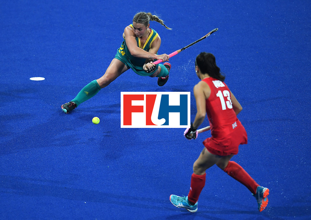 Australia's Mariah Williams (L) hits the ball as Britain's Sam Quek looks on during the women's field hockey Britain vs Australia match of the Rio 2016 Olympics Games at the Olympic Hockey Centre in Rio de Janeiro on August, 6 2016. / AFP / MANAN VATSYAYANA        (Photo credit should read MANAN VATSYAYANA/AFP/Getty Images)