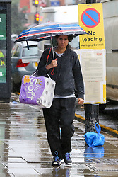 © Licensed to London News Pictures. 27/06/2020. London, UK. A woman shelters from rain underneath an umbrella in north London following a very hot week which saw highest temperature of the year so far. Photo credit: Dinendra Haria/LNP