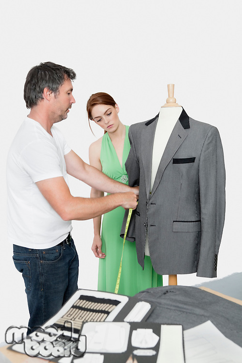 Male tailor taking measurement of suit while female coworker standing besides